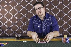 A man playing poker sitting at a table Stock Images