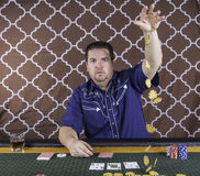 A man playing poker sitting at a table Royalty Free Stock Images