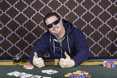 A man playing poker sitting at a table Stock Image