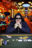 A man playing poker sitting at a table Royalty Free Stock Photo