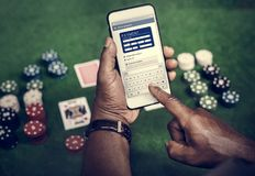 A man playing poker and using mobile. To transfer money through online banking Stock Images