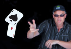Man playing Poker with Winning Aces. Man wearing sunglasses and cap throwing winning poker hand of two aces Royalty Free Stock Image