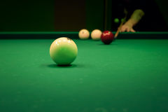Man playing in pool billiards on green table Royalty Free Stock Images