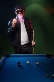 Man playing pool in a club smoking a cigarette Royalty Free Stock Photo