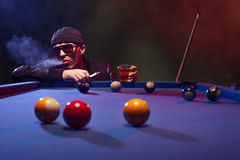Man playing pool in a club smoking e-cigarette Stock Image