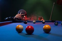 Man playing pool in a club smoking e-cigarette Stock Photography