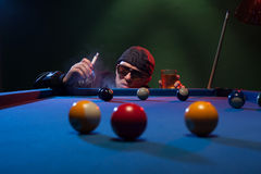 Man playing pool in a club smoking e-cigarette Stock Images