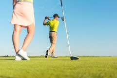 Man playing professional golf with his partner during matchplay. Low-angle full length view of men playing professional golf with his female partner during Stock Photography