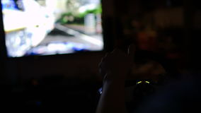 Man playing racing game with steering wheel in. Back close-up shot of a man playing car racing with steering wheel in darkness. Big screen with game action stock footage