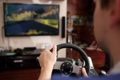 Man playing racing game with steering wheel Stock Image