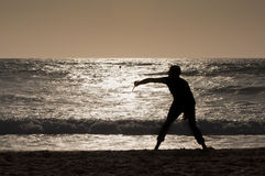 Man playing with racket at sunset. In the beach Stock Image