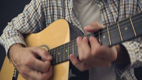 Man playing rock tune on acoustic guitar stock footage