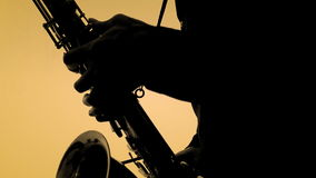 Man playing sax in silhouette. Close-up