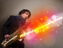 Man playing on saxophone with colorful sound waves Stock Photos