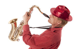 Man playing saxophone with devotion. Male entertainer playing a brass tenor saxophone with silver valves and pearl buttons leaning backwards Royalty Free Stock Images
