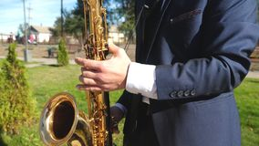 A man playing saxophone jazz music. Saxophonist in dinner jacket play on golden saxophone. Live performance. Man playing saxophone jazz music. Saxophonist in stock footage