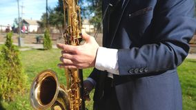 A man playing saxophone jazz music. Saxophonist in dinner jacket play on golden saxophone. Live performance. Man playing saxophone jazz music. Saxophonist in stock photography