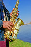Man playing the saxophone on the riverbank Stock Photo