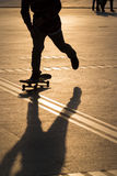 Man playing skateboard. Silhouette of man playing skateboard in park Royalty Free Stock Images