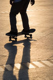 Man playing skateboard. Silhouette of man playing skateboard in park Stock Photo