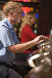 Man Playing Slot Machines. Man in casino playing slot machine with people in background royalty free stock images