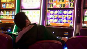 Man playing at slot machines. In casino stock video