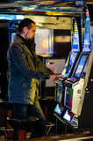 Man playing at slot machines Stock Photos