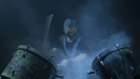 The man is playing snare drum in blue light background. stock footage