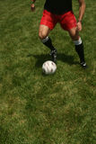 Man playing soccer juggling ball. Man playing soccer juggling soccer ball on the green grass Royalty Free Stock Photography