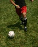Man playing soccer juggling ball. Man playing soccer juggling soccer ball on the green grass Stock Images