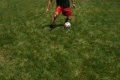Man playing soccer juggling ball. Man playing soccer juggling soccer ball on the green grass Stock Photography