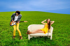 Man playing a solo on the guitar with girl lying on the couch  Stock Photography