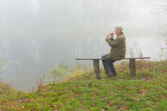 Man playing sopilka while sitting on a bench on the riverside Royalty Free Stock Photos