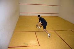 Man playing squash. Striking the ball Stock Images
