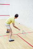 Man playing squash. Back view of squash player in action reaching on squash court. Squash player in action on a squash court motion blurred image. Squash player Royalty Free Stock Image