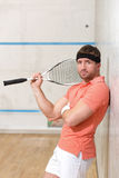 Man playing squash. Handsome man looking at camera after playing squash on court. Serious man in orange t-shirt and white shorts posing near wall in gym Royalty Free Stock Photography