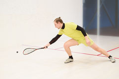 Man playing squash. Young caucasian squash player hitting a ball in a squash court. Squash player in action. Man playing match of squash. Sports activities Stock Photos