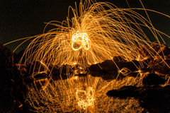 A man playing steel wool on the beach at  night. A man playing steel wool on the beach at night Stock Photo