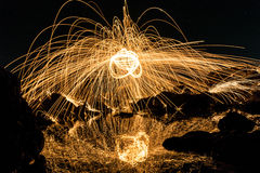 A man playing steel wool on the beach. At night Stock Photos