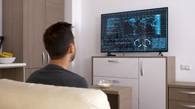 Man playing a strategic video game on the console. On big screen TV. Back view. Dolly slider 4K footage stock video footage