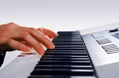 Man playing on a synthesizer,  on a gradient gray Stock Photo