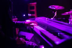 Man playing on synthesizer keyboard on stage during concert. Backlight, colors intentionally altered royalty free stock photos