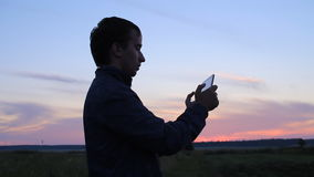 A man playing on a tablet in the game. Against the backdrop of a beautiful sunset sky stock footage