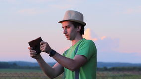 A man playing on a tablet in the game. Against the backdrop of a beautiful sunset sky stock video