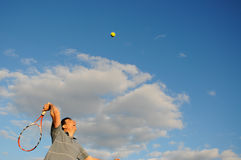 Man playing tennis. Action shot of man smashing tennis ball royalty free stock image