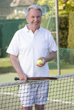 Man playing tennis and smiling royalty free stock image