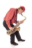 Man playing tenor saxophone bend over. Male performer playing a brass tenor saxophone with silver valves and pearl buttons with bending forward Royalty Free Stock Photography