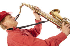 Man playing tenor saxophone enthousiastically. Male performer playing a brass tenor saxophone with silver valves and pearl buttons with expression Stock Photography