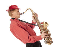 Man playing tenor saxophone leaning backwards. Male performer playing a brass tenor saxophone with silver valves and pearl buttons leaning backwards Royalty Free Stock Image