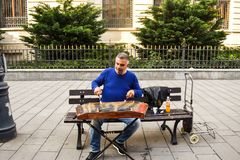 Man playing traditional hammered dulcimer with mallets. Street artist plays songs on the Bucharest`s streets in downtown. royalty free stock photos